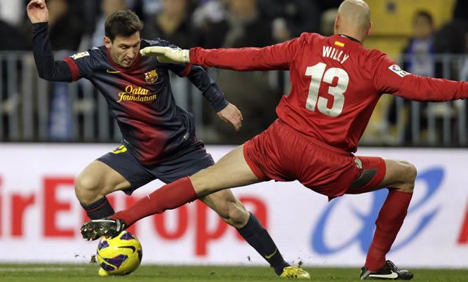 El delantero argentino del Barcelona Lionel Messi consigue el primer gol para su equipo tras regatear al guardameta argentino del Málaga, Wilfredo Daniel Caballero durante el partido que enfrenta a ambos equipos en la decimonovena jornada de la Liga de Primera División en el estadio de la Rosaleda en Málaga