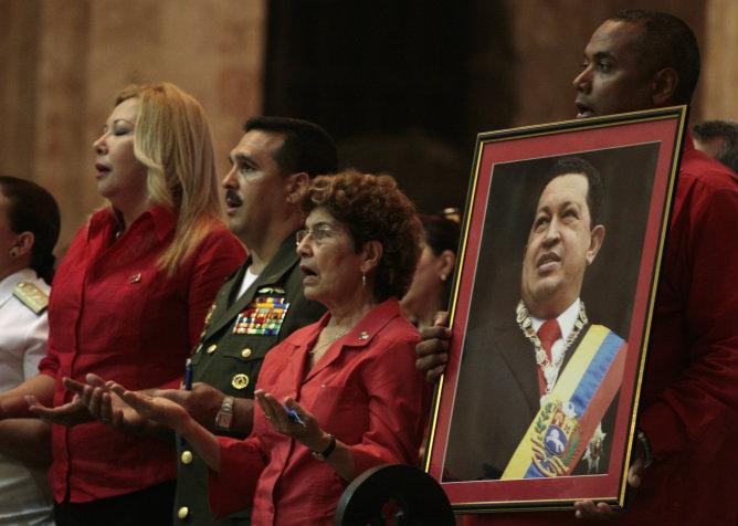 Un hombre venezolano sostiene un retrato del presidente Hugo Chávez durante la misa multitudinaria celebrada por la salud del comandante en La Habana
