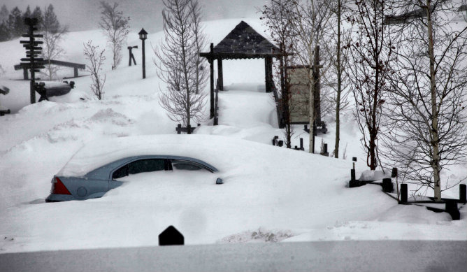 Un coche cubierto de nieve en un parque de Benasque