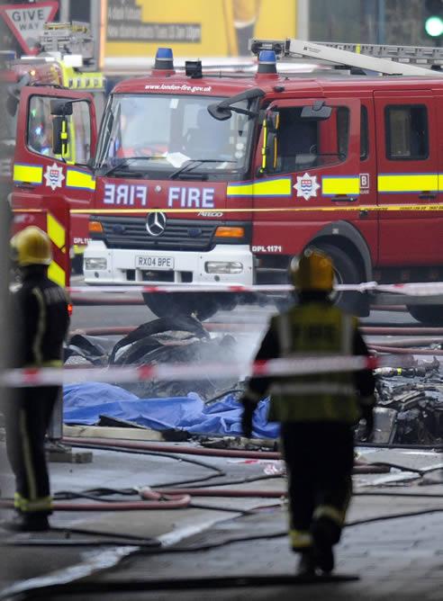 Bomberos y servicios de emergencia trabajan en el lugar donde se ha estrellado un helicóptero en el centro de Lonres (Reino Unido)