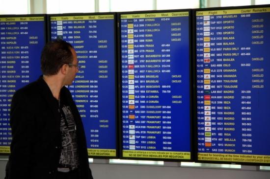 Un viatger mira el panell informatiu a l'Aeroport del Prat