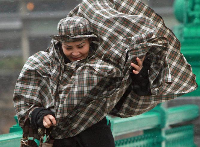 Una mujer se protege del viento y de la lluvia en San Sebastián