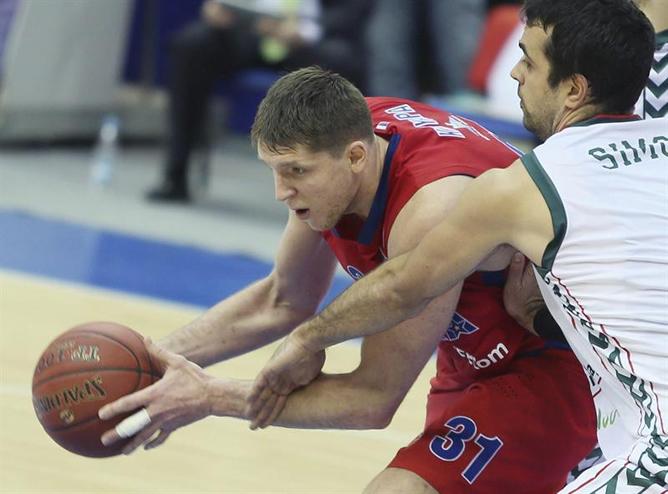 El jugador del CSKA Moscú, Viktor Khryapa (i), lucha por el balón con Krunoslav Simon, del Unicaja, durante el partido de Euroliga que ambos equipos han disputado en Moscú