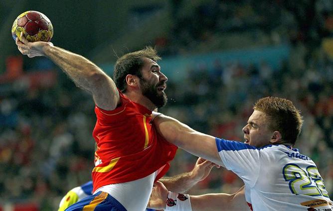 El central de España Joan Cañellas Reixac (i) lanza ante la oposición del pivote de Eslovenia Matej Gaber durante la semifinal del Campeonato del Mundo de balonmano España 2013