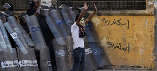Un manifestante intenta detener el lanzamiento de piedras contra los policías en los  enfrentamientos de Alejandría.