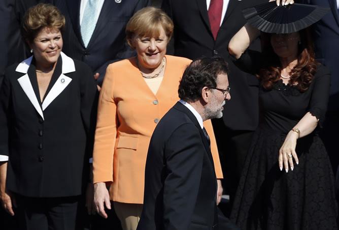 El presidente del Gobierno, Mariano Rajoy pasa ante la canciller alemana, Angela Merkel, antes de la foto de familia en la cumbre chilena.