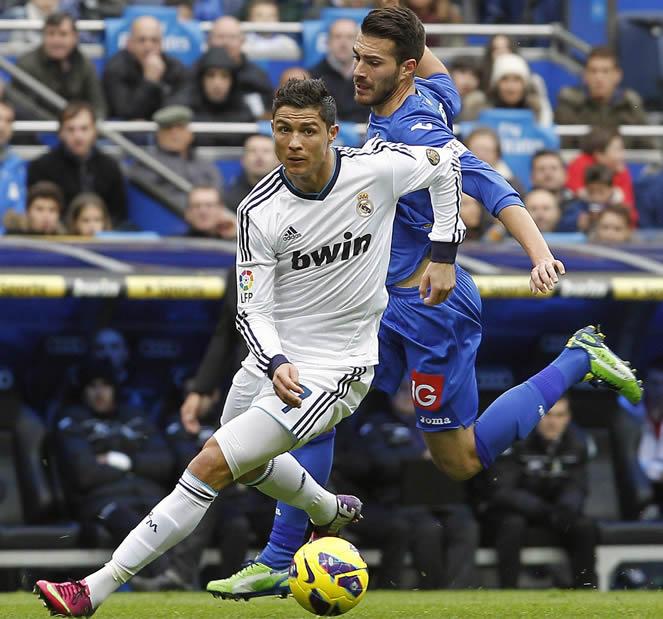 El delantero portugués del Real Madrid, Cristiano Ronaldo, se marcha del defensa del Getafe, Rafa López, durante el partido correspondiente a la vigésimo primera jornada de la Liga de fútbol de Primera División que los dos equipos disputaron en el estadio Santiago Bernabéu, en Madrid