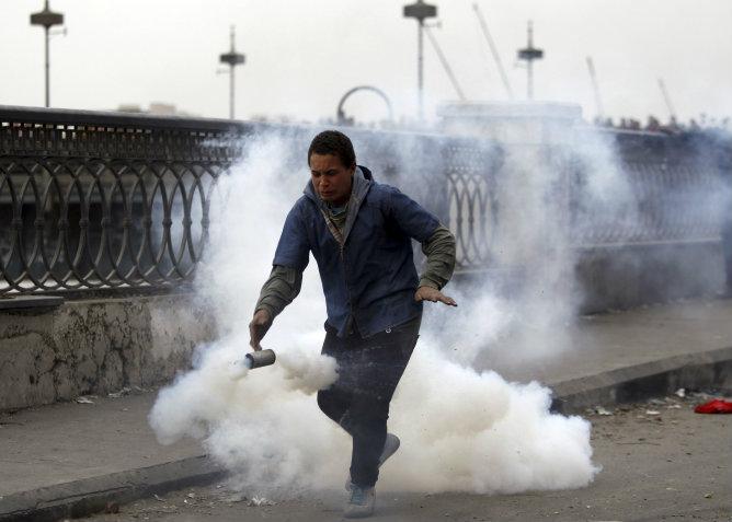 Un opositor del presidente Mohamed Mursi huye del gas lacrimógeno lanzado por la policía en el puente Qasr Al Nil, puente que conduce a la plaza Tahrir en El Cairo