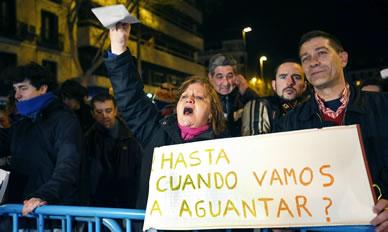 Varias personas muestran pancartas durante una concentración en la que varios centenares de asistentes han protestado contra la corrupción en la sede del PP en Madrid.