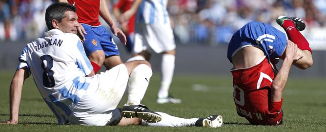 El delantero portugues del Real Zaragoza Hélder Postiga cae tras una jugada con el centrocampista francés del Málaga Jéremy Toulalan, durante el partido de la décimosegunda jornada de la Liga de Primera División, que ambos equipos disputan este mediodía, en el estadio de la Rosaleda en Málaga
