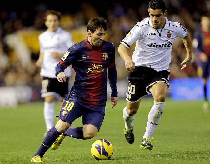 Leo Messi controla el balón ante el defensa portugués del Valencia Ricardo Costa
