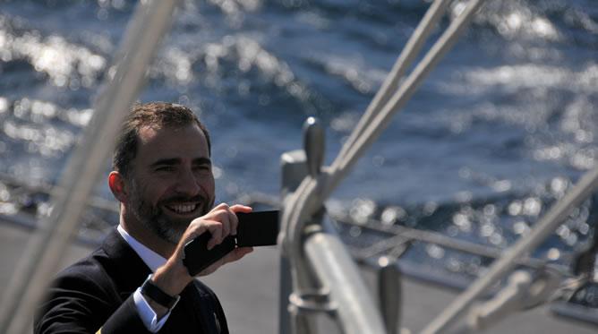 El príncipe Felipe despide y fotografía con su móvil al portaviones que lleva su nombre en la base naval de Rota