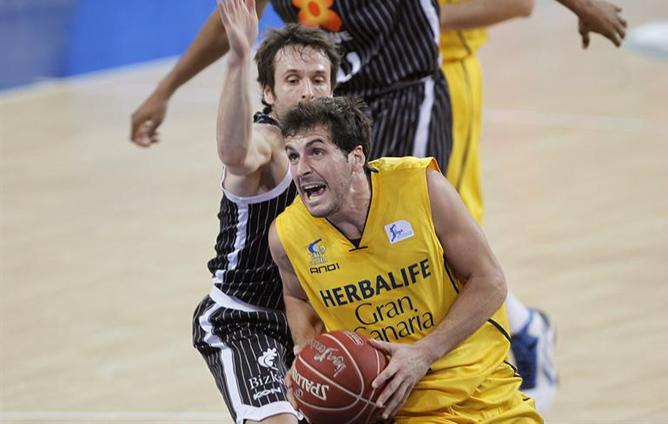 El base del Herbalife Gran Canaria, Tomás Bellas, controla el balón bajo la presión del base del Uxue Bilbao Basket Raúl López durante el partido de cuartos de final de la Copa del Rey de baloncesto.