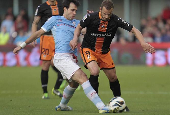 El centrocampista del Celta de Vigo Borja Oubiña y el delantero del Valencia Roberto Soldado luchan por el balón durante el partido correspondiente a la vigésimo tercera jornada de Liga de Primera División.