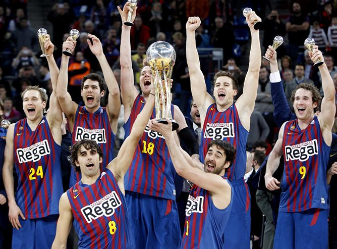 Los jugadores del Regal Barcelona Víctor Sada y Juan Carlos Navarro levantan el trofeo que acredita al club azulgrana vencedor de la Copa del Rey de baloncesto tras vencer por 85 a 69 al Valencia Basket en la final disputada esta tarde en el Buesa Arena de Vitoria.