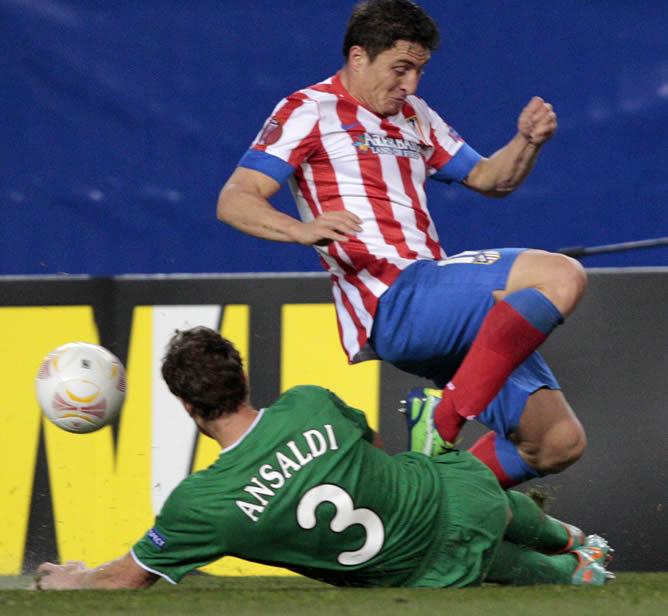 El centrocampista uruguayo del Atlético de Madrid Cristian Rodríguez pelea un balón con el defensa argentino del Rubin Kazan Cristian Ansaldi, durante el partido de ida de dieciseisavos de final de la Liga Europa de fútbol que se disputa en el estadio Vicente Calderón