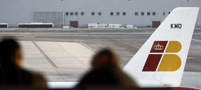 Dos personas ante un avión de Iberia en el aeropuerto de Barajas