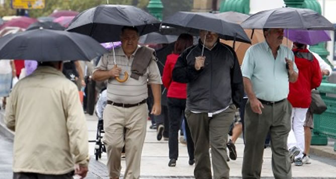 Varios viandantes se protegen de la lluvia durante este fin de semana en San Sebastián