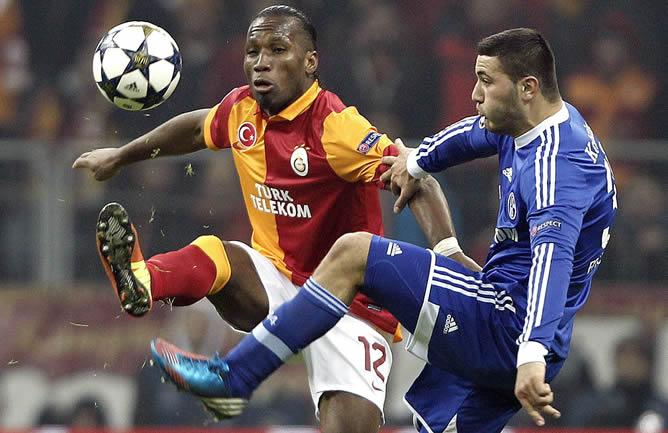 El jugador del Galatasaray Didier Drogba disputa el balón con Sead Kolasinac del Schalke este miércoles 20 de febrero de 2013, durante el partido de octavos de final de la Liga de Campeones de la UEFA en el Turk Telekom Arena de Estambul (Turquía)
