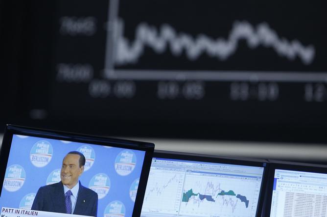 Imagen de Silvio Berlusconi en una pantalla de televisión y al fondo la cotización del DAX alemán