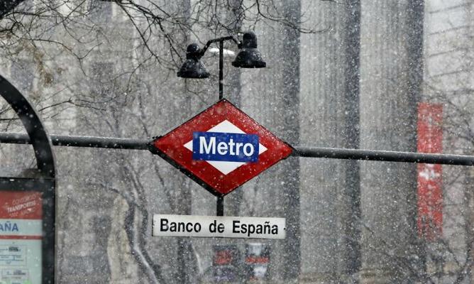 Vista de la estación de Metro de Banco de España durante la nevada que cae hoy sobre la capital