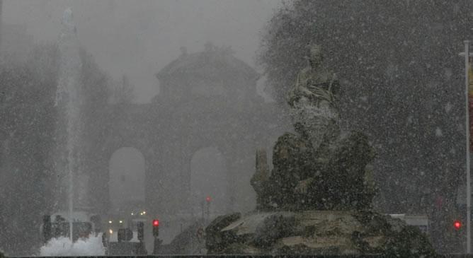 Vista de la madrileña fuente de Cibeles, con la puerta de Alcalá al fondo, bajo la nevada que ha caído este pasado miércoles sobre la capital