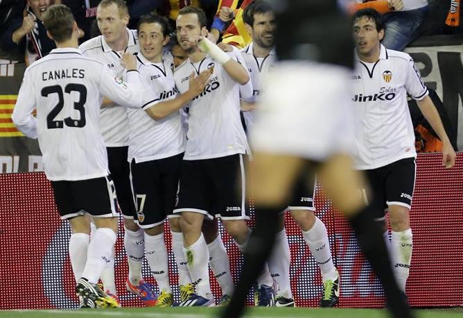 El delantero del Valencia CF Roberto Soldado celebra su gol, segundo de su equipo, con sus compañeros durante el partido ante el Levante en Mestalla.