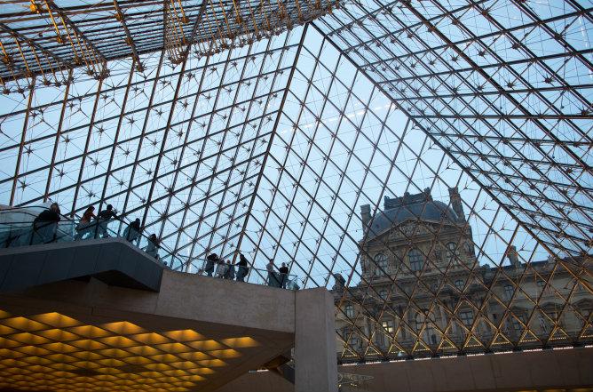 Un grupo de turistas visita la pirámide de vídrio y metal del Louvre