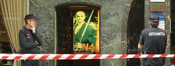 La Policía científica de la Ertzaintza custodia el gimnasio de artes marciales de Bilbao en el que han aparecido restos óseos en bolsas de plástico, y que es propiedad del maestro shaolín detenido, cuya imagen aparece en el cartel