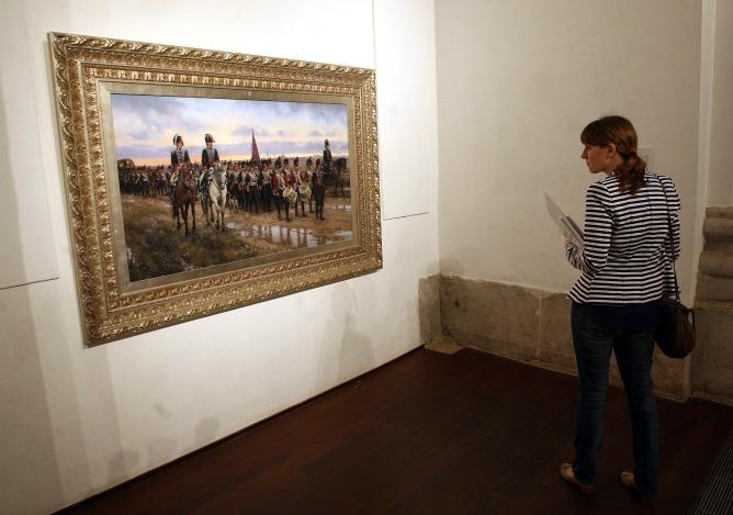 """Una espectadora de la exposición """"Soldados de España en la Historia"""" contempla una de las obras"""