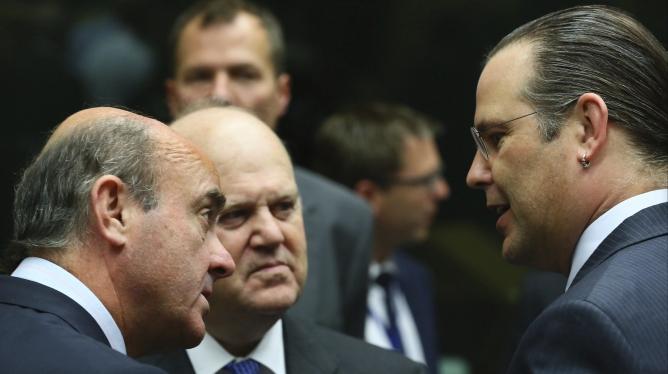 El ministro español de Economía, Luis de Guindos, habla con sus homólogos irlandés, Michael Noonan, y sueco, Anders Borg, al inicio de la reunión de los ministros de Economía de la UE en Bruselas