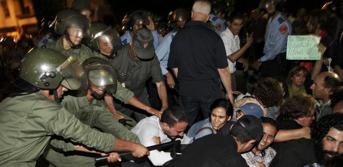 Los manifestantes chocan con la policía antidisturbios durante una manifestación en contra de un indulto real por un pedófilo español en Rabat