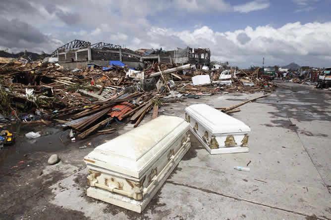 Ataúdes vacíos en una calle cerca de las casas dañadas de la ciudad de Tacloban tras el paso del tifón