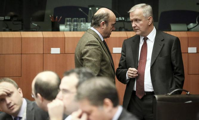 El vicepresidente de la Comisión Europea Olli Rehn conversa con el ministro español de Economía, Luis de Guindos (c), antes del inicio de la reunión de ministros de Finanzas de la UE en Bruselas