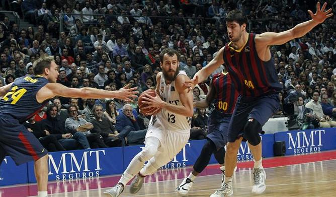 El base del Real Madrid Sergio Rodríguez entra a canasta ante los jugadores del F.C. Barcelona Ante Tomic y Brad Oleson, durante el partido correspondiente a la decimotercera jornada de Liga ACB.
