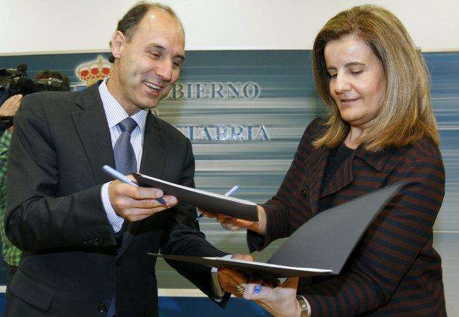 La ministra de Empleo y Seguridad Social, Fátima Báñez, intercambia documentos con el presidente cántabro, Ignacio Diego, durante la firma de un convenio en materia de lucha contra la economía sumergida