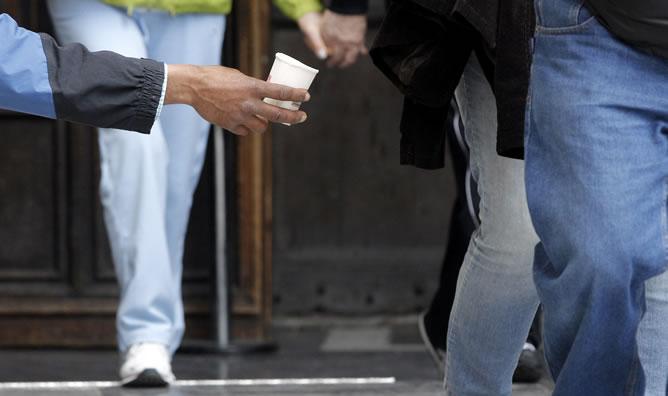 Un hombre pide dinero en la calle