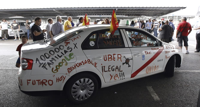 """Uno de los taxis que muestran con pintadas su descontento y que junto con centenares de taxistas de toda España han participado hoy en Madrid en la manifestación convocada por el sector, en coincidencia con las 24 horas de huelga de protesta por el intrusismo y la """"ilegalidad"""" de aplicaciones de teléfonos móviles como Uber, convertidas en su principal competencia."""