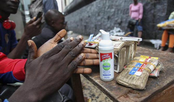Un comerciante de moneda liberiano se lava las manos para prevenir el ébola