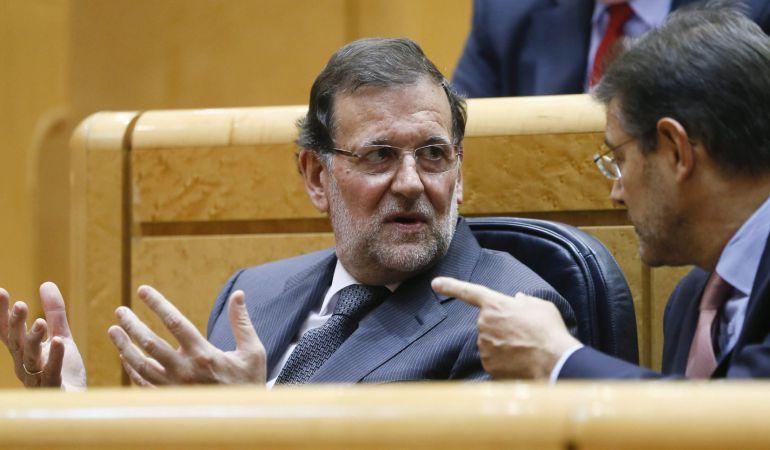 El presidente del Gobierno, Mariano Rajoy, conversa con el ministro de Justicia, Rafael Catalá.