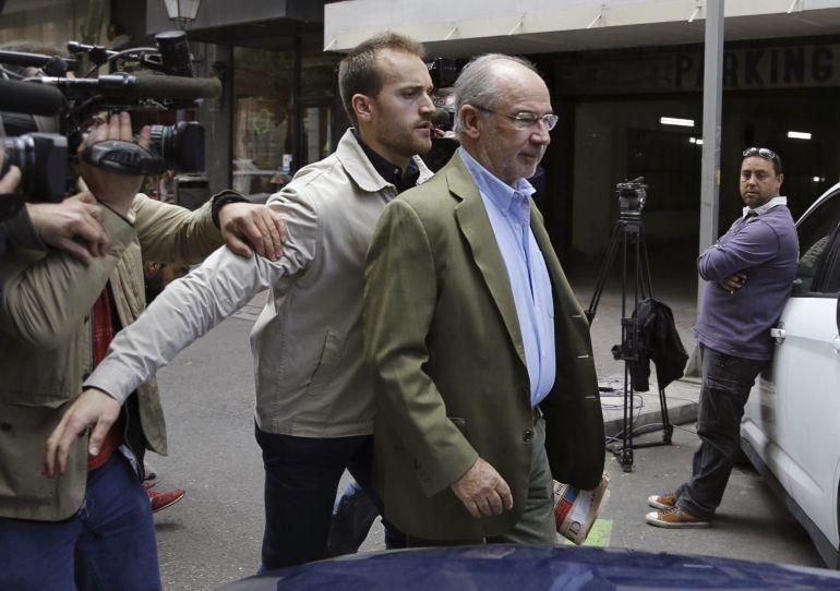 El exvicepresidente del Gobierno, Rodrigo Rato, acompañado de un guardaespaldas, sale de su domicilio donde numerosos medios de comunicación esperan noticias