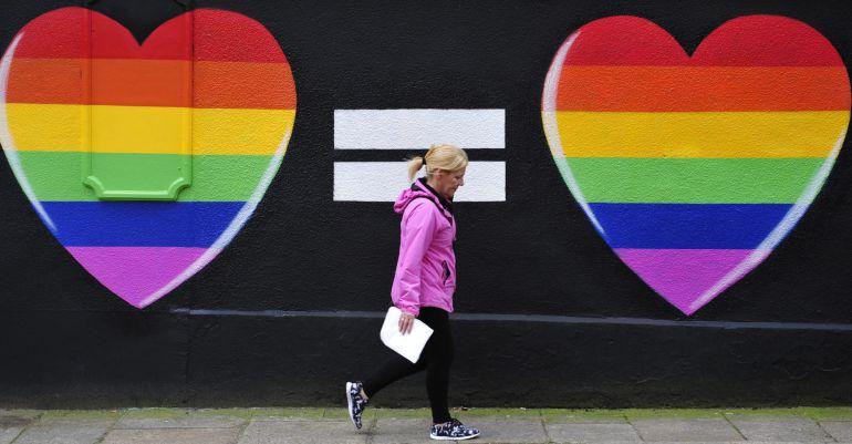 Una mujer camina junto a una pintada de dos corazones con los colores del arcoíris en Dublín, Irlanda.