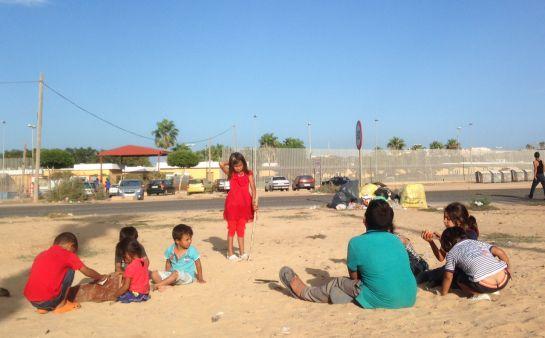Niños sirios juegan al atardecer en la puerta del Centro de Estancia Temporal de Inmigrantes de Melilla que, con 1.700 internos, está al triple de su capacidad