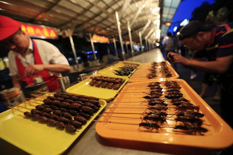 Vista de pinchos de escorpiones, grillos, cigarras y otros bichos disponibles en el puesto del vendedor Zheng Zhongbin en el mercado nocturno de Donghuamen.