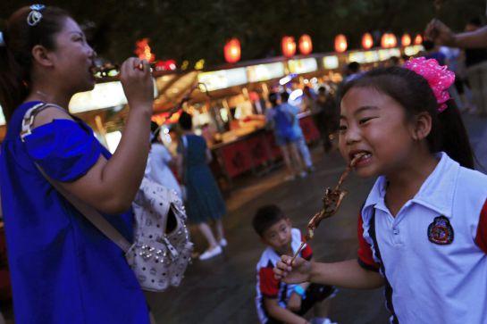 Varios visitantes prueban pinchos de marisco de un puesto del mercado.