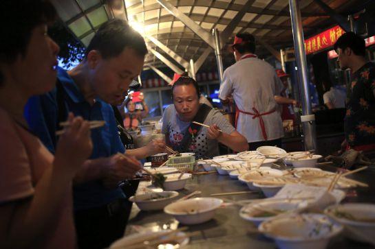 Varios visitantes cenan en un puesto en el mercado nocturno de Donghuamen.