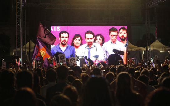 Simpatizantes de Unidos Podemos escuchan las declaraciones de su líder Pablo Iglesias.