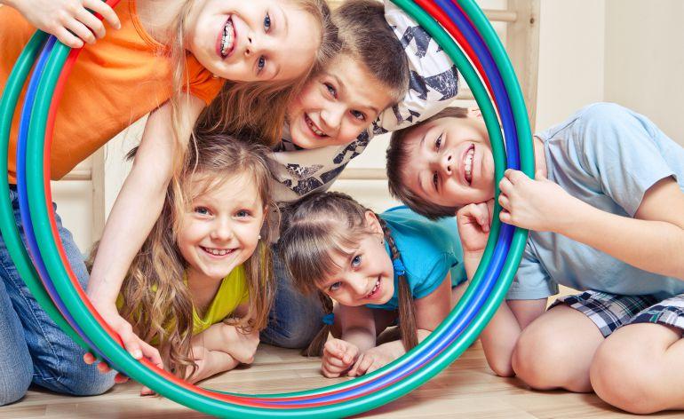Un grupo de niños observa sonriente a través de varios aros de juego.