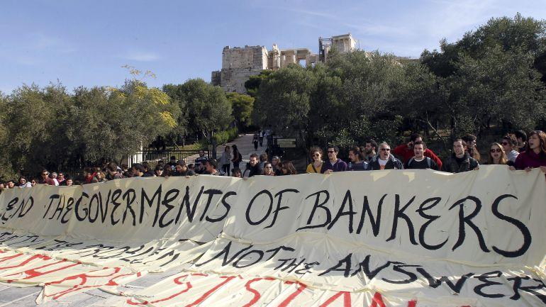 """Manifestantes y afiliados a la Coalición de Izquierda radical (SYRIZA) sostienen una pancarta en la que se lee """"Acabemos con el gobierno de los bancos. La austeridad es el problema, no la respuesta"""" durante una protesta en la entrada de la Avcrópolis en Atenas en noviembre de 2011."""