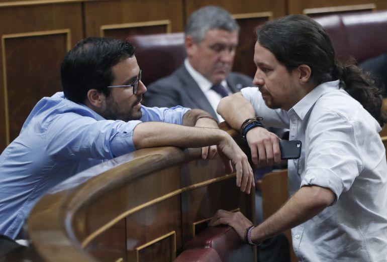 El líder de Podemos, Pablo Iglesias (d), conversa con el diputado de Unidos Podemos Alberto Garzón, durante la sesión de la tarde de la segunda jornada del debate de investidura del candidato del PP, Mariano Rajoy